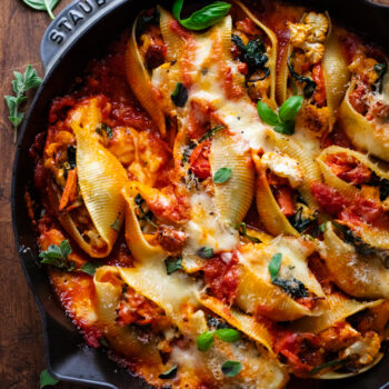 vegetarian stuffed shells in a skillet pan that is arranged on a wooden background. Fresh herbs are arranged around the skillet and sprinkled over top of the stuffed shells.