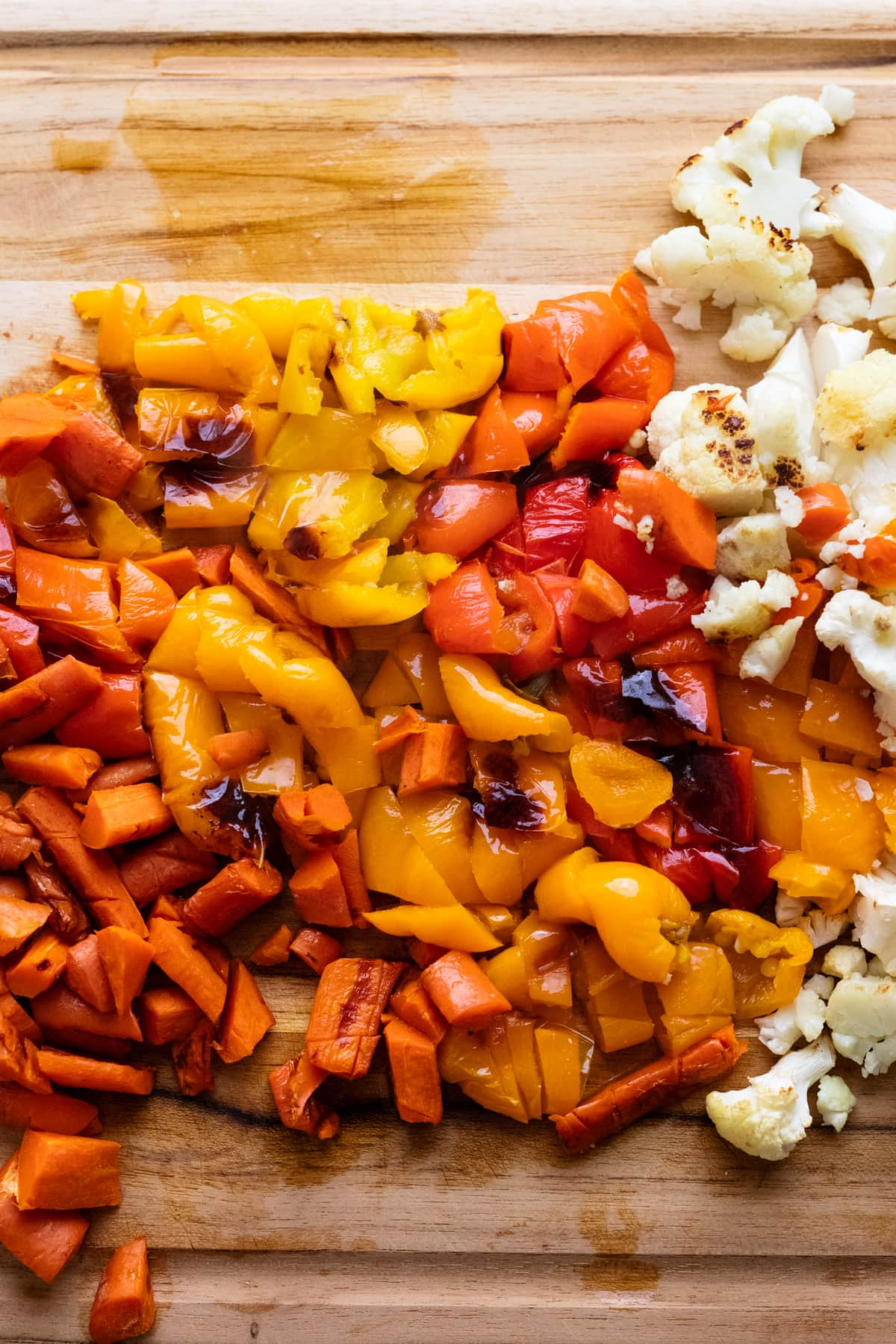 Chopped roasted vegetables on a wooden cutting board.