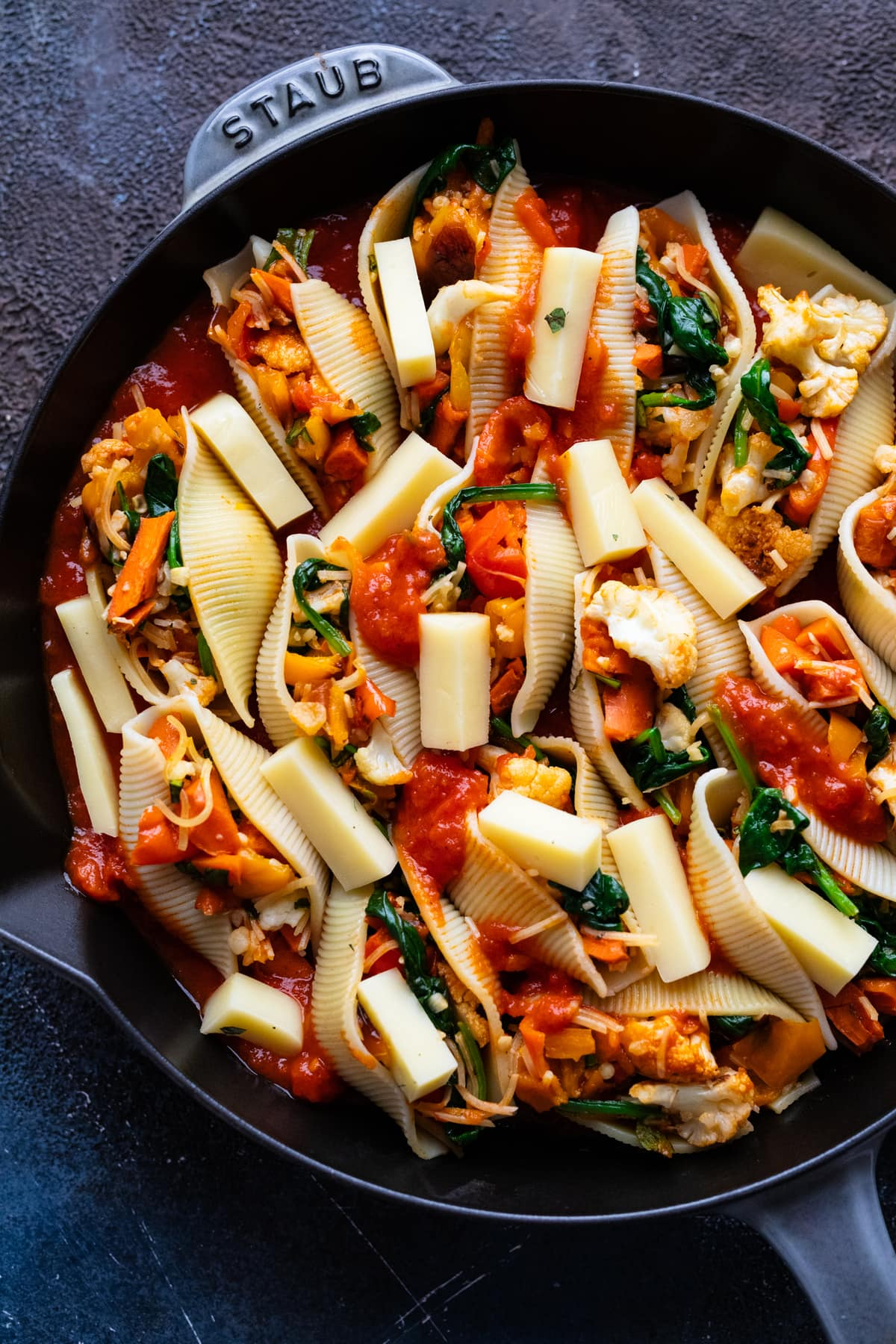 Vegetarian stuffed shells and pieces of cheese in a cast iron pan.