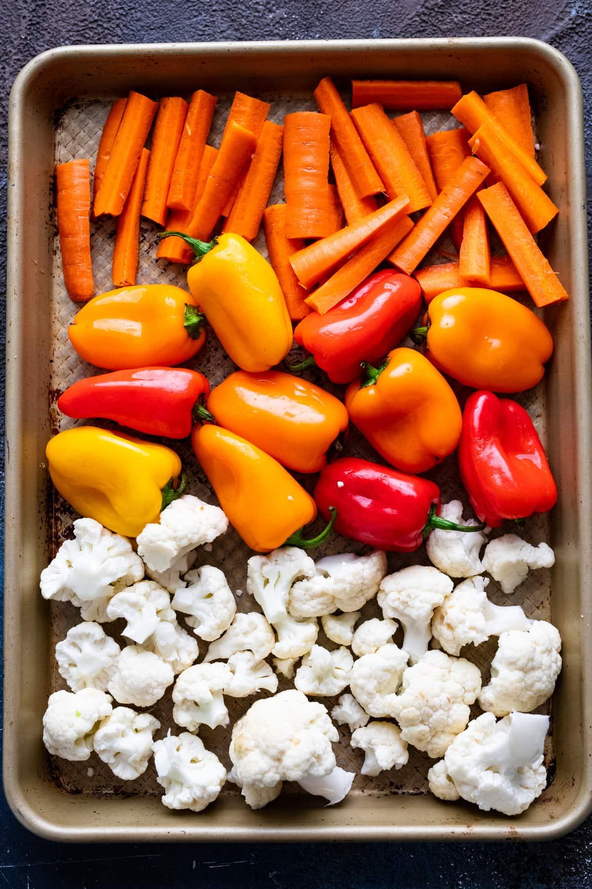 An assortment of vegetables arranged on a sheet pan.