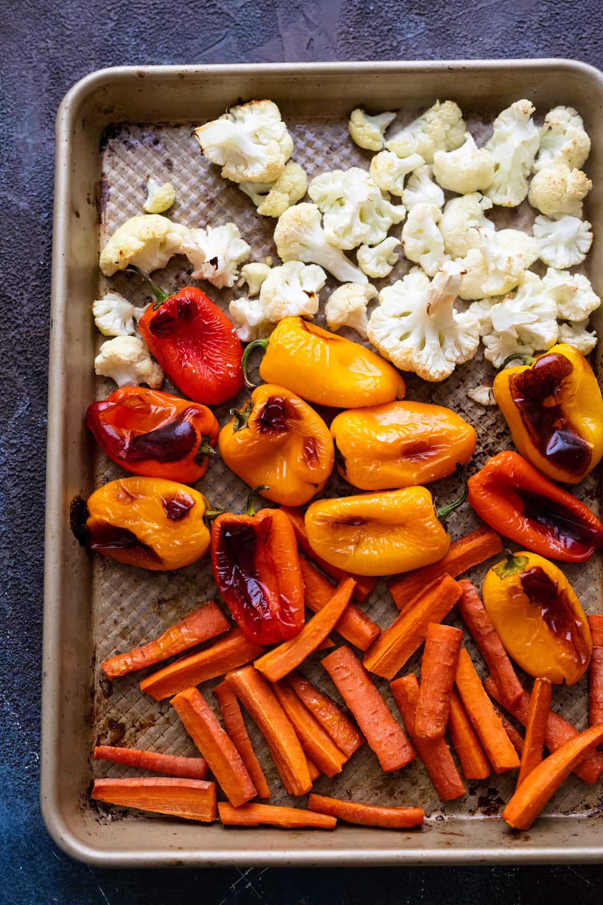 An assortment of roasted vegetables on a sheet pan.
